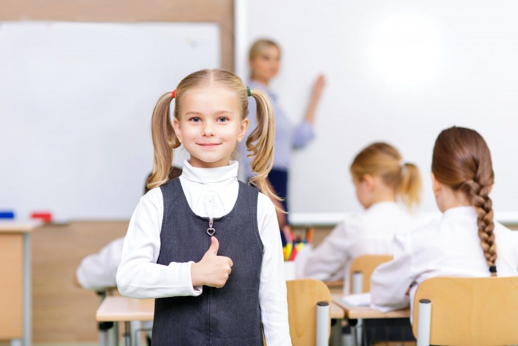 Little girl standing in the classroom