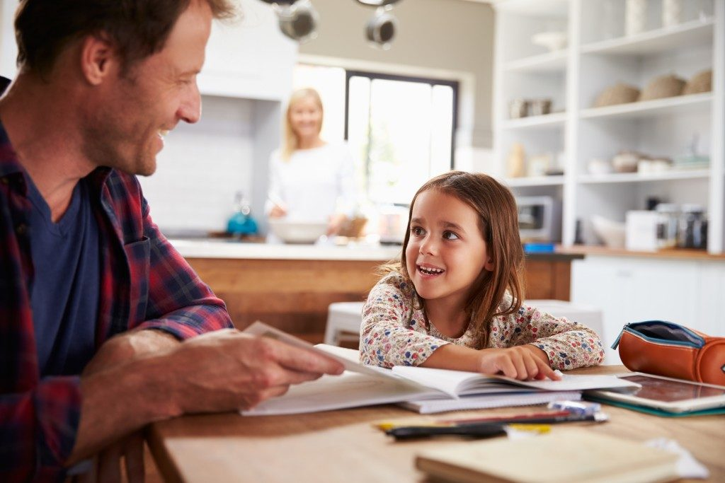 Father doing schoolwork with daughter