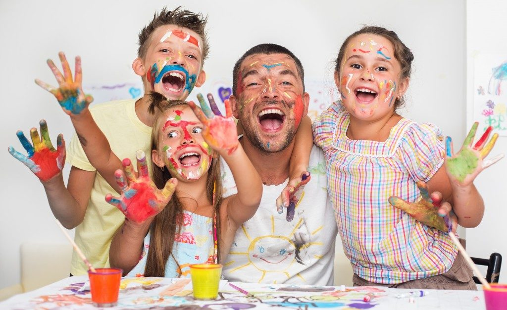 Children playing with paint with dad