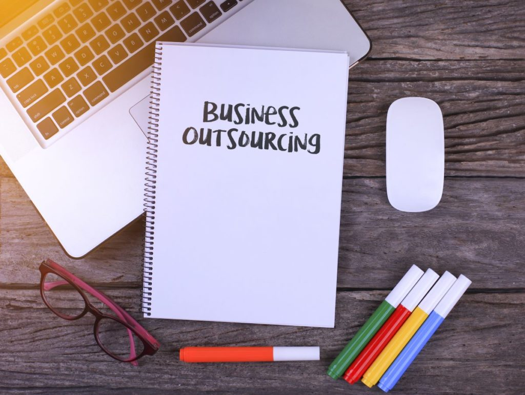 Notebook writing Business Outsourcing, Office table with laptop ,coffee cup,glasses